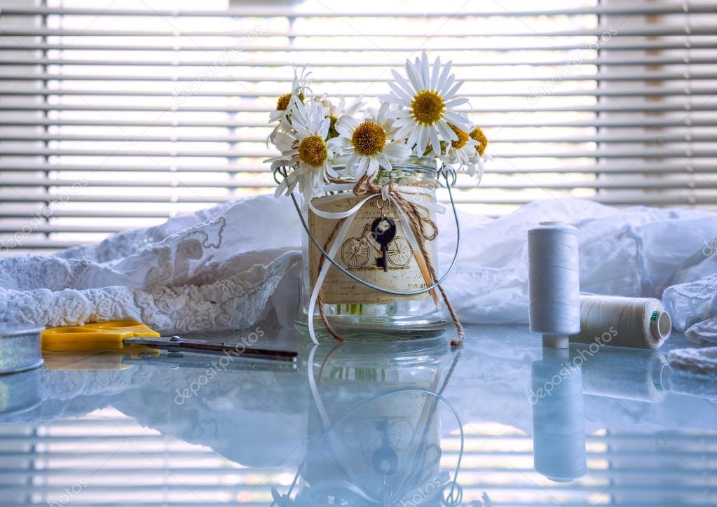 Bouquet von Gänseblümchen in Glasvase, Thread, Spulen, Schere auf ...