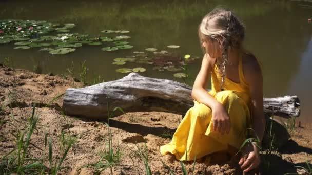 Krásná dívka v žlutých letní šaty sedí u jezírka s lekníny