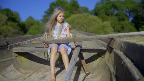 cute little girl in an old boat with hair flying in the wind. cinemagraph - motion photo seamless loop