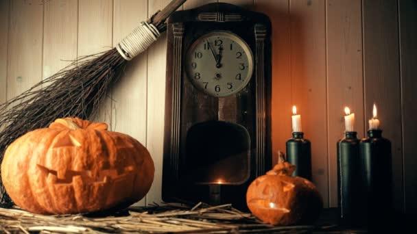 půlnoc na Halloween. dýně, svíčky a hodinky. čarodějka ruku, přičemž koště