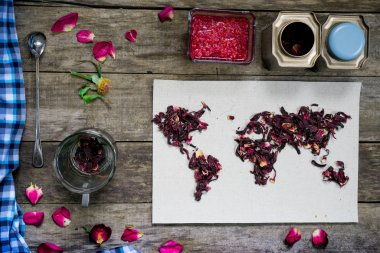 map of the world, lined with tea leaves on old paper. Eurasia, America, Australia, Africa. vintage. hibiscus tea, cup, a towel, raspberry jam on rustic wooden table. top view. flat lay