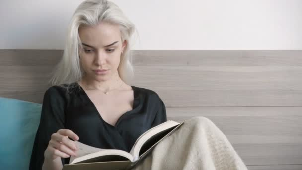 Attractive beautiful girl reading in bed at morning