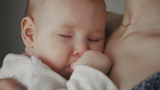 Mladá matka drží své novorozené dítě spí. Rodina doma