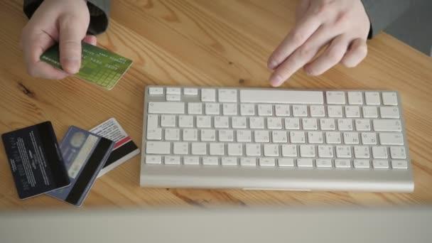 Rövid idő használ a Laptop a fából készült asztal hivatalban hitelkártya pillantást üzletember. Szemközti nézet.