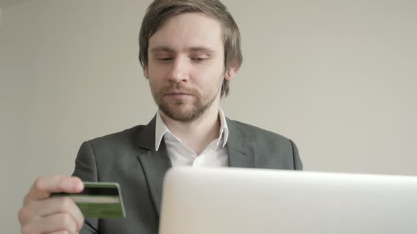 Rövid idő használ a Laptop a fából készült asztal hivatalban hitelkártya pillantást üzletember. Elölnézet.