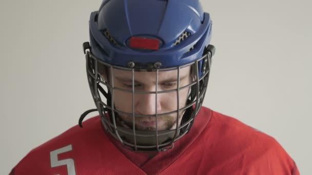 Closeup portrét hokejista v helmě proti bílé pozadí