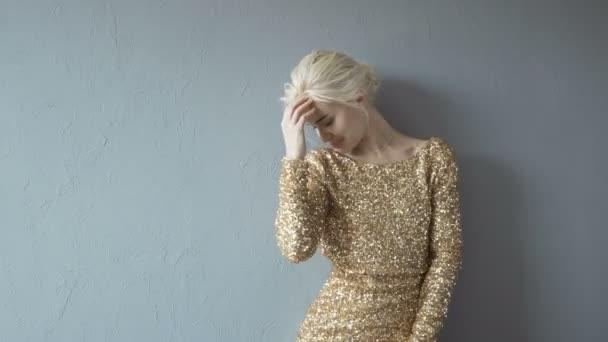 Portrét krásné Sexy mladá blondýna v lesklých šatech izolovaných na Gray
