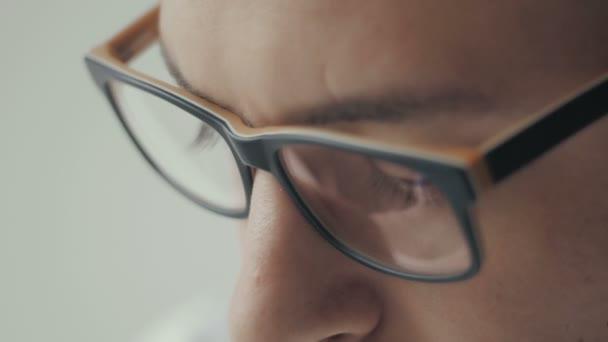 Zblízka portrét mladých obchodní muž nosí brýle s bočním výhledem na záři