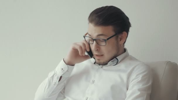 Portrait of Young Man In Glasses Talking on The Phone Against White Background