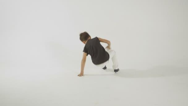 Malý stylový chlapec Break Dance a baví, izolované na Whitestudio Shot