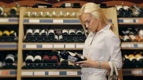 Mladá krásná žena vybírá víno v supermarketu