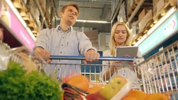 Zákazníci nakupování v supermarketu a kontrolu seznam výrobků na Tablet Pc, pohled z nákupního vozíku