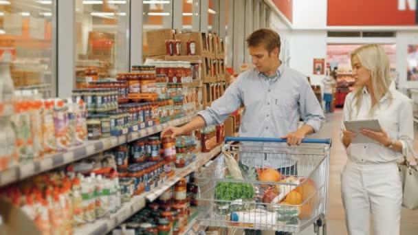 Zákazníci nakupování v supermarketu a kontrolu seznam výrobků na počítači Tablet Pc