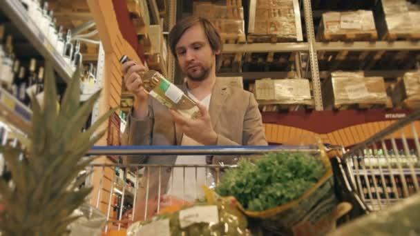 Pohledný muž, nakupování v supermarketu, pohled z nákupního vozíku