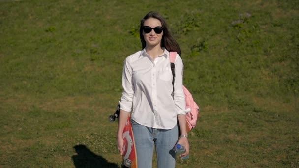 Mladá Sexy dívka venkovní módní portrét. Krásný stylový ženské skateboardista nosí sluneční brýle v parku