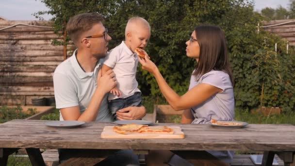 Mladá rodina s piknik v zahradě. Máma, táta a syn jíst pizzu venku
