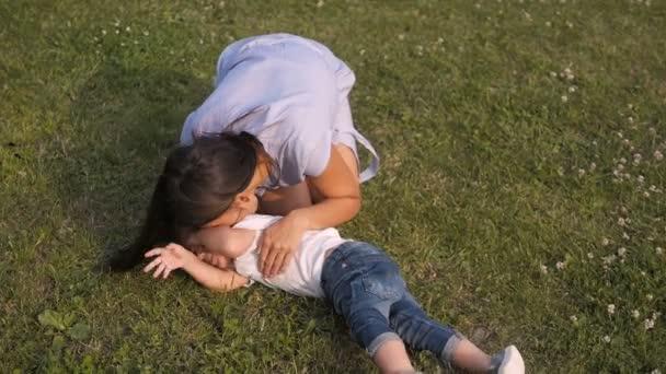 Matka a její syn mají zábavu na trávě v parku. Mami, lechtání a líbání syn