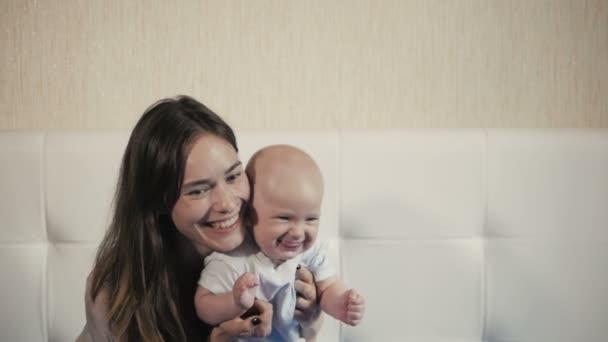 šťastné rodinné rozesmáté tváře, matka hospodářství roztomilé dítě chlapeček, usmíval se a objímání, hranice, vypadá krásy úsměvu, ženské izolovaných na bílém, radostné matka zdravé dítě, vyjadřující emoce lásky