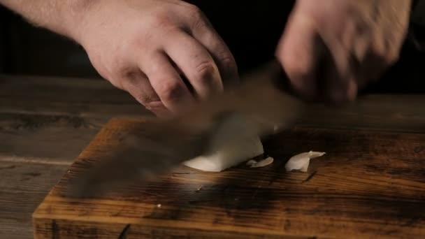 Close - Up náčelníci rukou řezání cibule na dřevěném prkénku