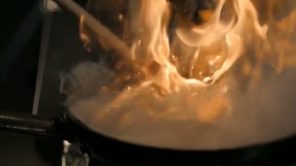 Kuchař, vaření s ohněm při smažení Pan.Professional šéfkuchaře v komerční kuchyni vaření Flambe stylu. Vaření hovězí Stroganoff.
