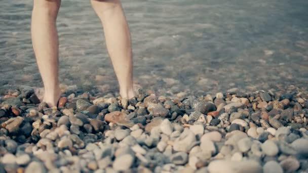 I piedi di un giovane come lui è in piedi sulla spiaggia