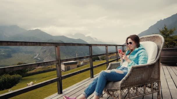 Žena turistické stylové oblečení na sobě střílí video z krásné horské krajiny na mobilní telefon, bokovky dívka pořízení fotografie s fotoaparátem mobilního telefonu při sezení poblíž hory v chladné jaro