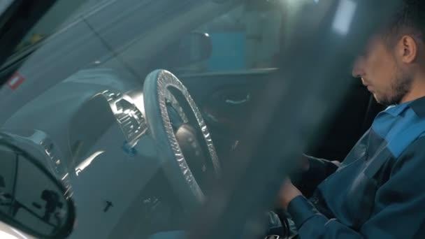 Szakmai autó szerelő dolgozik modern automatikus javítási szolgáltatást, és ellenőrzése a motor