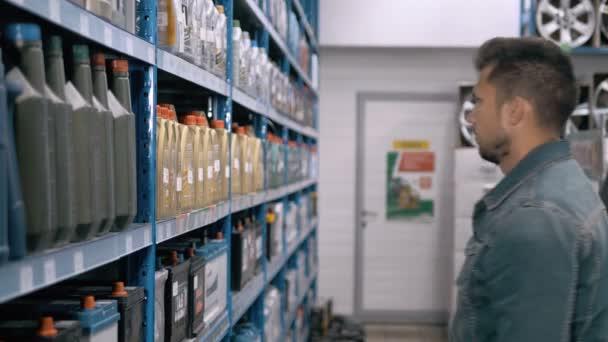 Auto mechanik muž zvolit moderní autobaterie pro vozík v supermarketu opravy čerpací stanice. Spousta zboží