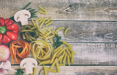 Spaghetti of different flowers and forms with vegetables and spices on a wooden background.