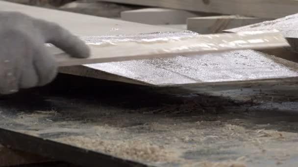 specialista s plochou holí rovnoměrně distribuuje tekuté lepidlo složení povrchu desky