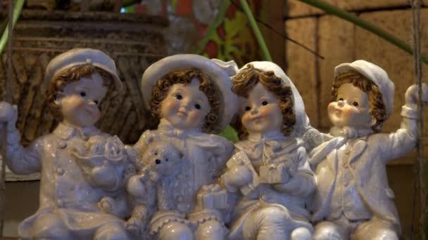 skleněné porcelánové panenky 4 lidí, kteří sedí na houpačce šťastně usmíval se vzájemně