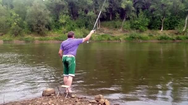 Mann angelt im Fluss in der Nähe des Wasserfalls