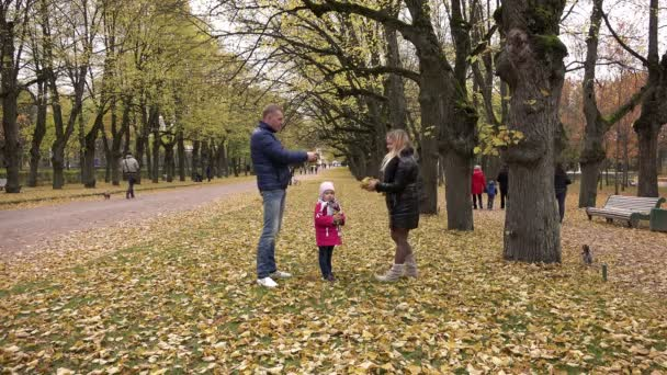 young family in park throwing up yellow leaves on the wind