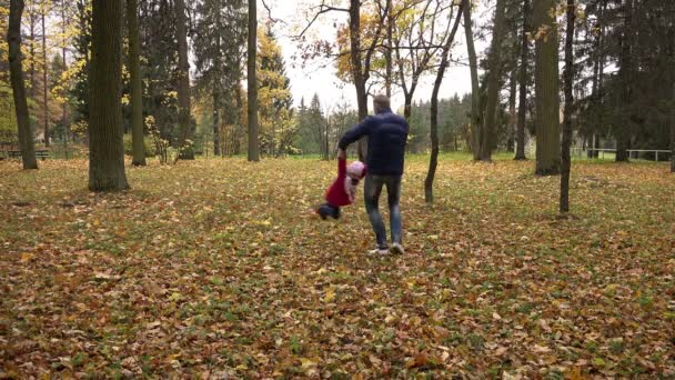father of the child turns to yellow foliage in the park