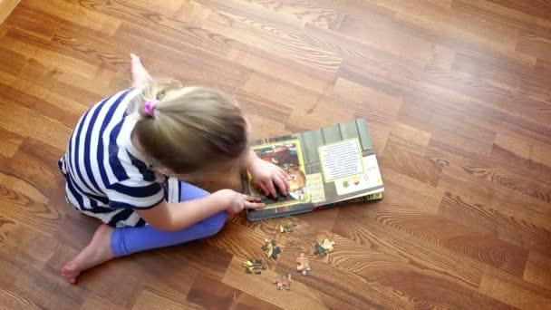 Rusko, Petrohrad, 14 březen 2015 - Girl klade mozaika kreslené postavičky v knize. Rychlá střelba