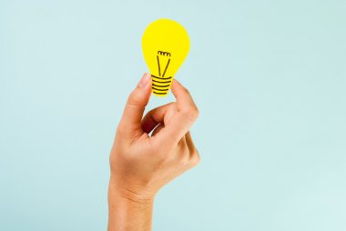 Brainstorming. Hand showing yellow lightbulb concept meaning a great idea.