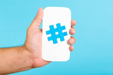 Hand showing a hashtag symbol / sign on white paper with phone mobile shape, with blue background. Internet, social media concept.