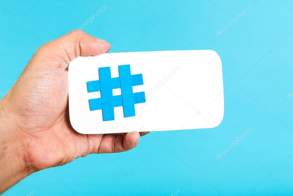 Hand showing a hashtag symbol / sign on white paper with phone mobile shape, with blue background. Internet, social media concept