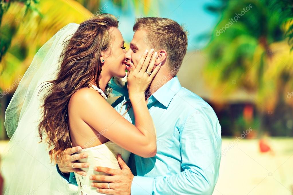 Kissing newlyweds on the beach