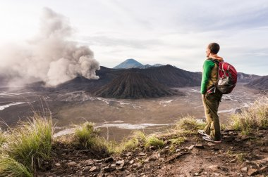Man on the hill is looking on Bromo volcano eruption. East Java, Indonesia