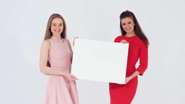 Dvě s úsměvem atraktivní dívky s prázdný nápis
