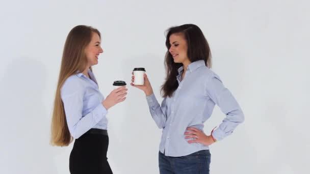 Dvě dívky usmívající se úřad v košile mluví a pití kávy