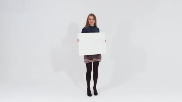 Usmívající se atraktivní dívka v hnědých šatech drží bílá transparent