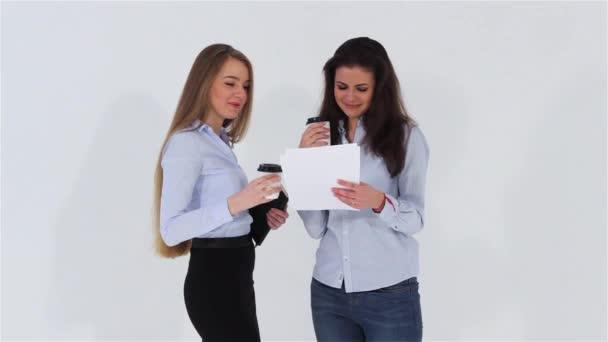 Dvě s úsměvem úřadu dívky povídají a pití kávy