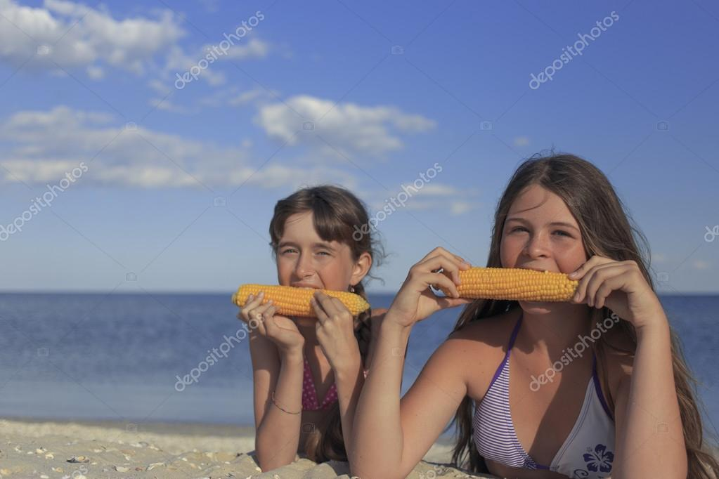 Happy children on the beach eating sweet corn.