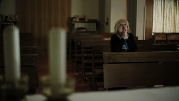 in der Kirche: Frau im Hintergrund betet: Kerzen, Katholiken, Glaube, Beten