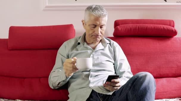 pohledný muž pít čaj na pohovce: červená, domů, sedí, sám, obývací pokoj