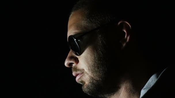Junger Mann nimmt in der Dunkelheit seine Sonnenbrille ab