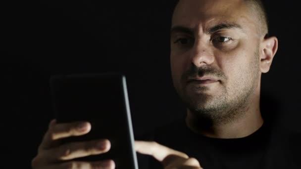 mladý muž používá smartphone hledání něco na webu, tablet pc