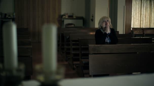 in der Kirche: Frau im Hintergrund betet: Religion, Katholiken, Glaube, Beten